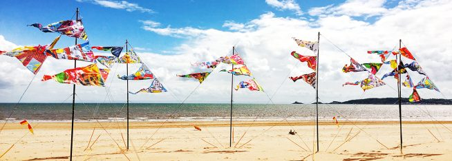 locws international art across the city swansea bay year of legends colourful flag installation in Swansea Bay