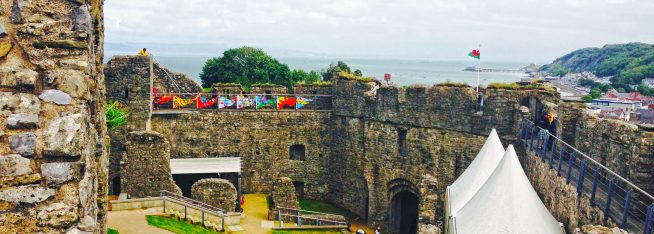 Locws International's Locws Schools project. Image featuring eight Year of Legends themed flags from each of the participating schools hung in the grounds of Oystermouth Castle with Mumbles Head depicted in the background.